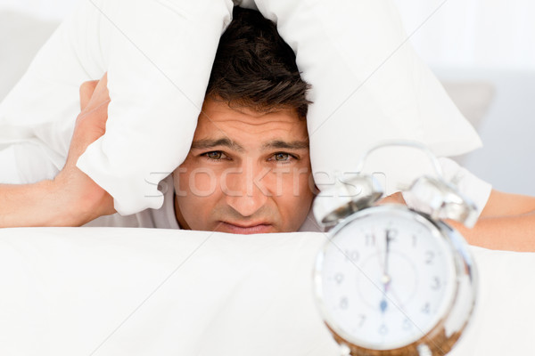 Sad man with head under the pillow waiting for his alarm clock Stock photo © wavebreak_media