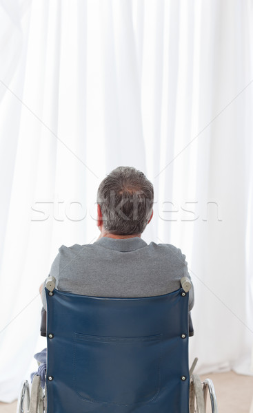 Mature man in his wheelchair with his back to the camera at home Stock photo © wavebreak_media