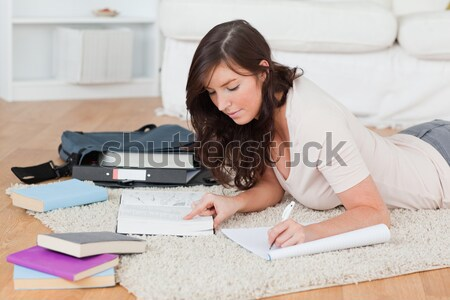 Attractive red-haired female reading a manual before do-it-yourself while lying on the floor at home Stock photo © wavebreak_media