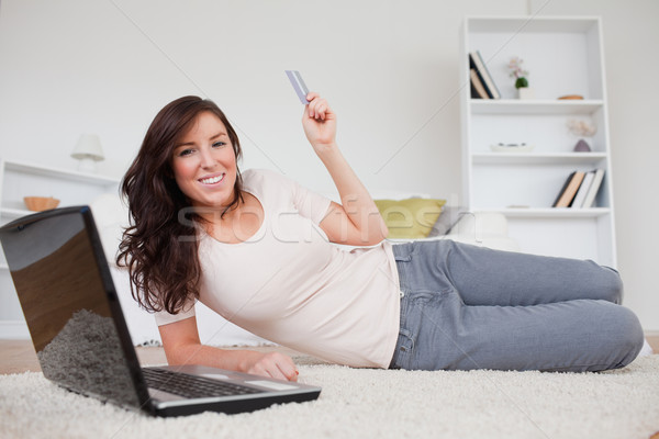 Attractive brunette female making a payment with a credit card on the internet while lying on a carp Stock photo © wavebreak_media