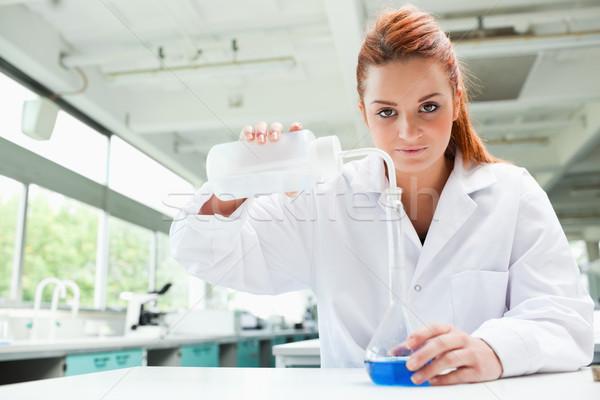 Tudós áramló folyadék flaska laboratórium nő Stock fotó © wavebreak_media