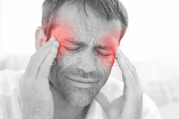 Man having a headache at home Stock photo © wavebreak_media