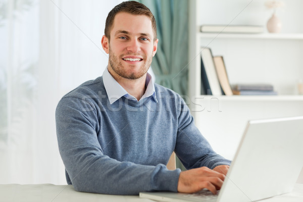 Smiling young businessman with laptop in his homeoffice Stock photo © wavebreak_media