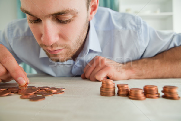 Young businessman counting coins Stock photo © wavebreak_media