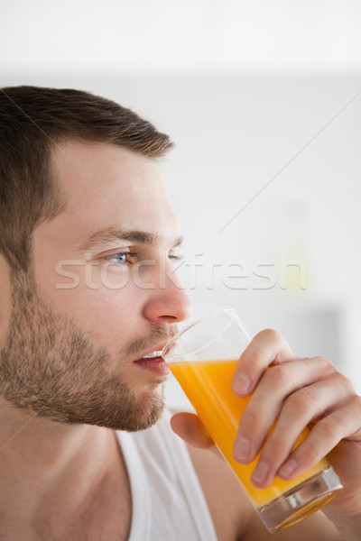 Close up of a man drinking orange juice in his kitchen Stock photo © wavebreak_media