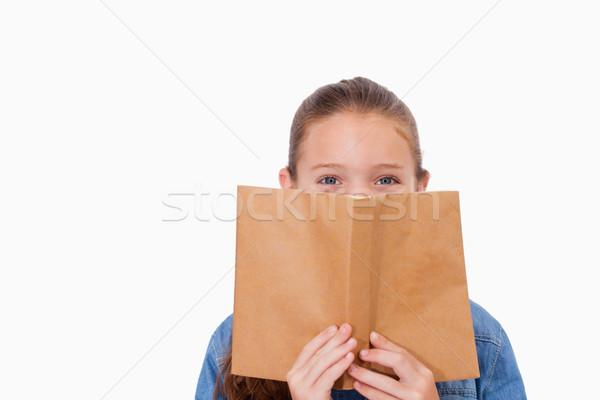 Nina ocultación cara detrás libro blanco Foto stock © wavebreak_media