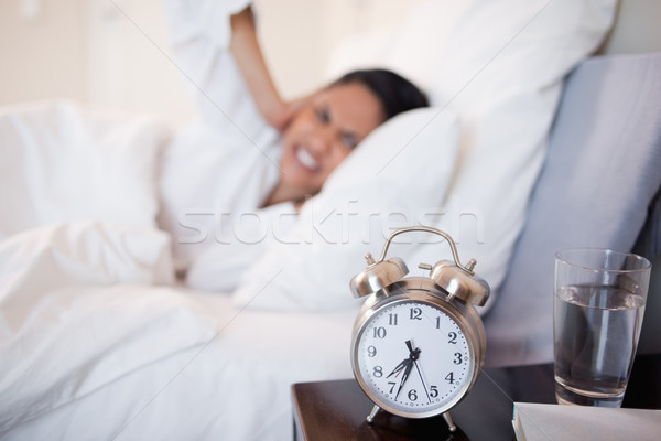 Alarm clock making young woman cover her ears Stock photo © wavebreak_media