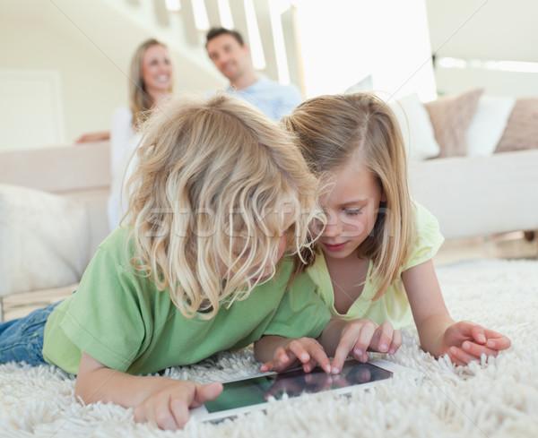 Broers en zussen vloer samen tablet ouders achter Stockfoto © wavebreak_media