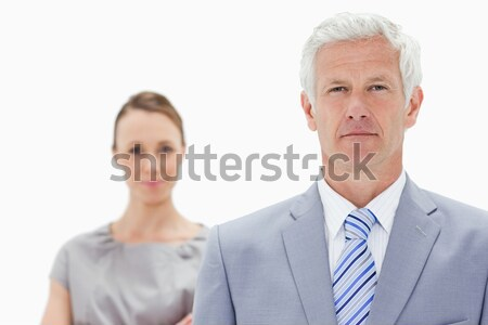 Close-up of a serious white hair businessman with a woman smiling behind him against white backgroun Stock photo © wavebreak_media