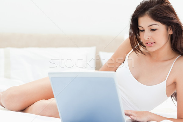 A woman using her laptop in front of her to browse while she lies on her bed. Stock photo © wavebreak_media
