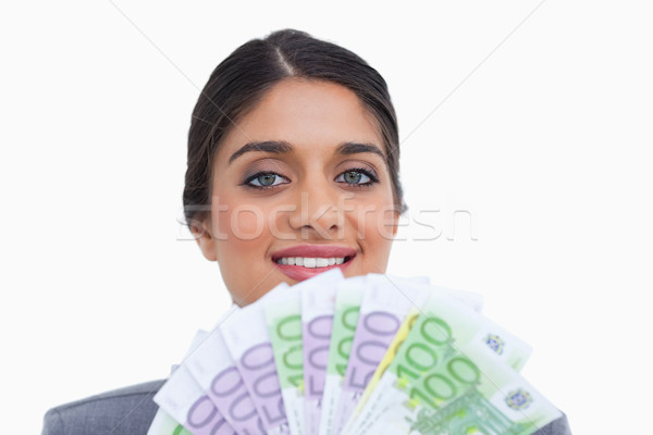 Close up of smiling female entrepreneur with bank notes against a white background Stock photo © wavebreak_media