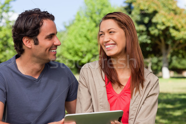 Woman looking at a man while she is holding a tablet in a sunny grassland environment Stock photo © wavebreak_media