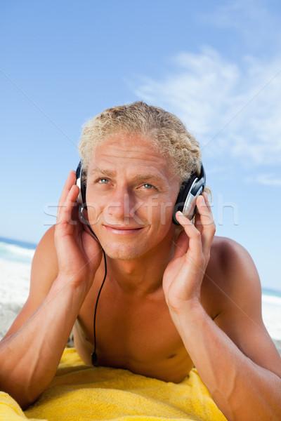 улыбаясь молодым человеком желтый пляжное полотенце пляж Сток-фото © wavebreak_media
