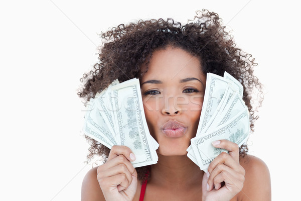Brunette woman puckering her lips while holding two fans of bank notes Stock photo © wavebreak_media