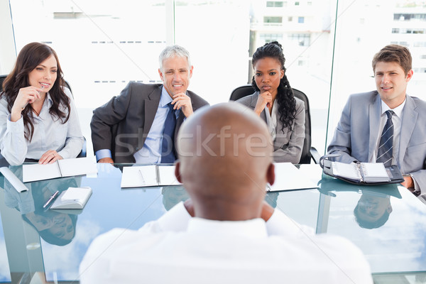 Stock photo: Four serious business people sitting at the desk while listening to explanations