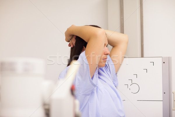 Patient placing her arms on her head while standing in front of a machine in an examination room Stock photo © wavebreak_media
