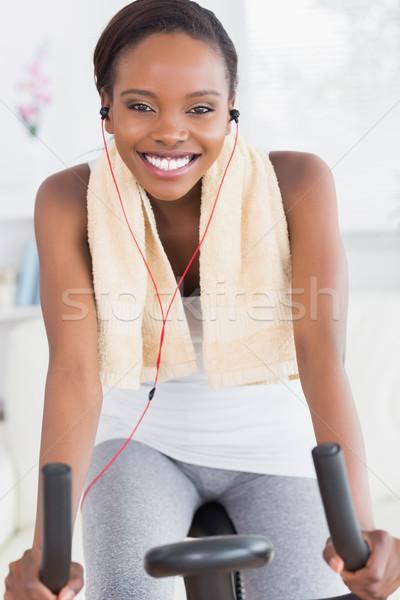 Black woman on an exercise bike listening music in a living room Stock photo © wavebreak_media
