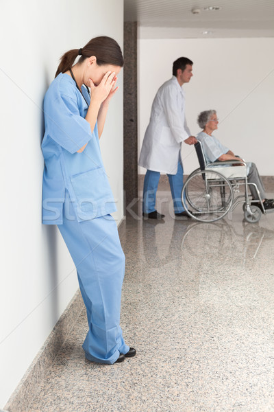 Stressed nurse leaning against wall with doctor pushing patient in wheelchair Stock photo © wavebreak_media