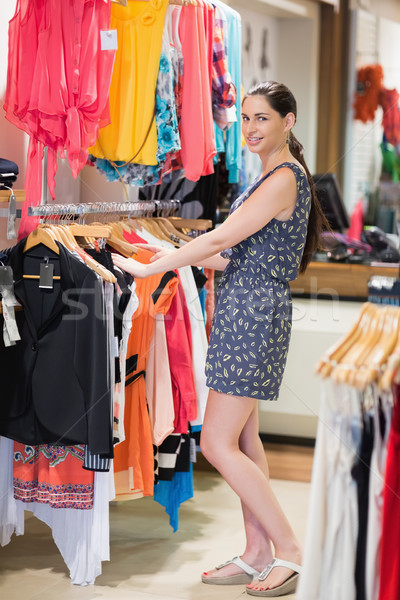 Woman is standing at the clothes rack smiling in the shop Stock photo © wavebreak_media
