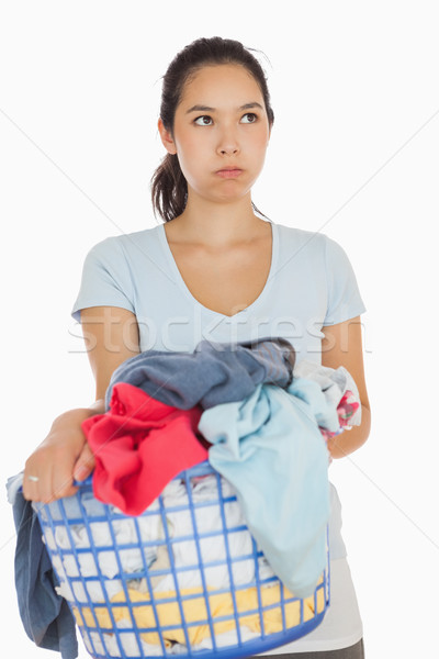 Exasperated woman holding a basket overflowing of laundry Stock photo © wavebreak_media