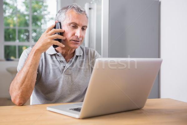 Olgun adam dizüstü bilgisayar kullanıyorsanız çağrı ev bilgisayar ev Stok fotoğraf © wavebreak_media