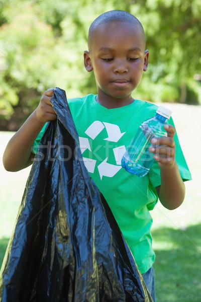 Little boy in recycling tshirt picking up trash Stock photo © wavebreak_media