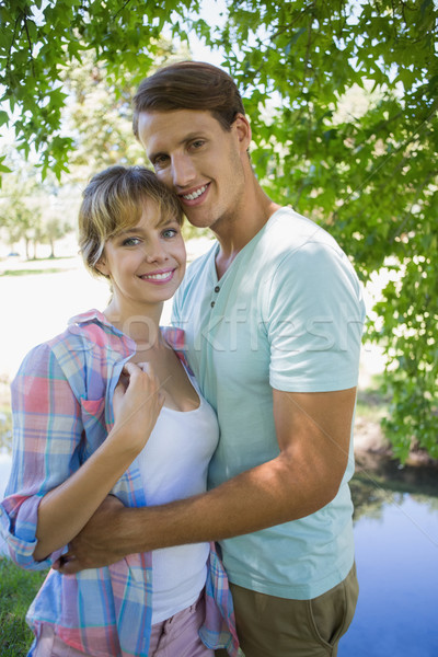 Loving young couple standing together in the park smiling at cam Stock photo © wavebreak_media