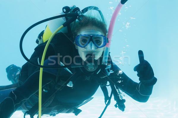 Woman on scuba training submerged in swimming pool showing thumb Stock photo © wavebreak_media