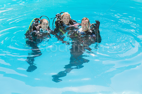 Stock photo: Smiling friends on scuba training in swimming pool