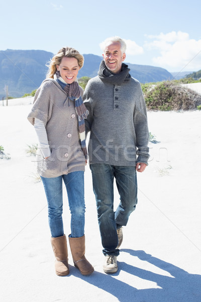 Smiling couple strolling on the beach in warm clothing Stock photo © wavebreak_media