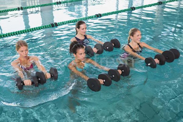Female fitness class doing aqua aerobics with foam dumbbells Stock photo © wavebreak_media
