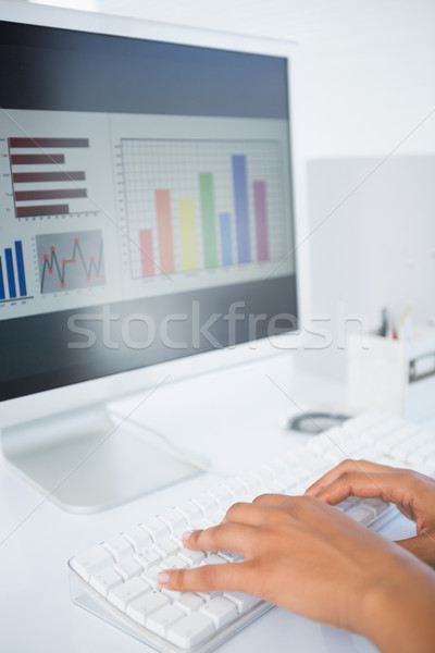 Businesswoman typing on a keyboard with data on screen Stock photo © wavebreak_media