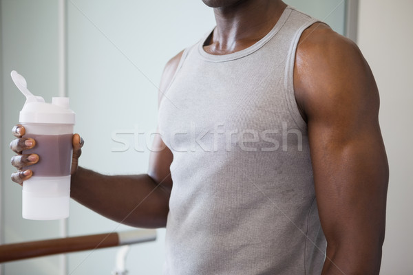 Sporty man holding protein drink in gym Stock photo © wavebreak_media