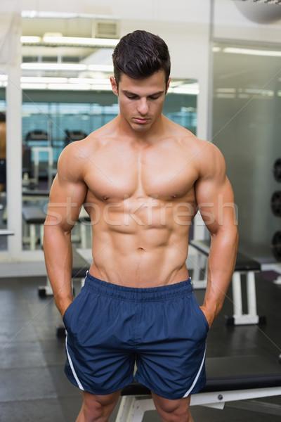Muscular hombre mirando hacia abajo sin camisa gimnasio sexy Foto stock © wavebreak_media
