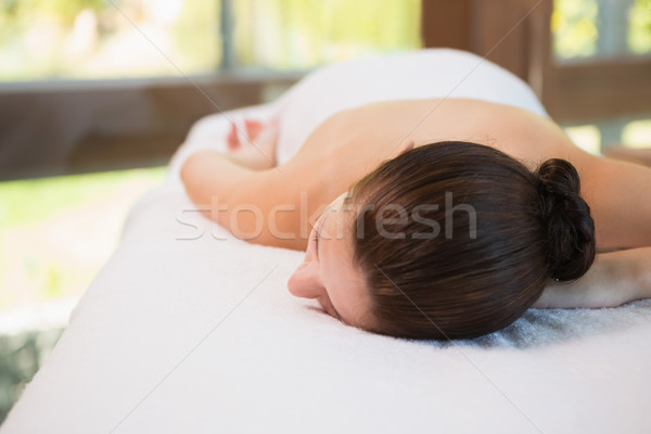 Stock photo: Beautiful woman lying on massage table at spa center