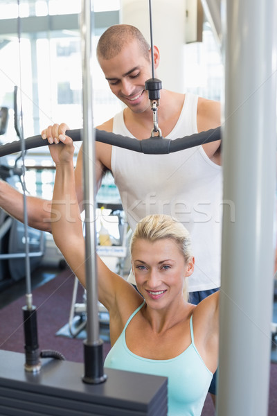 Male trainer assisting woman on lat machine in gym Stock photo © wavebreak_media
