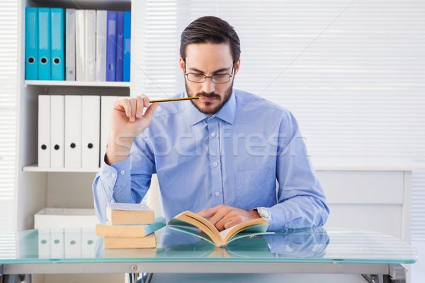 Focused businessman reading book at desk Stock photo © wavebreak_media