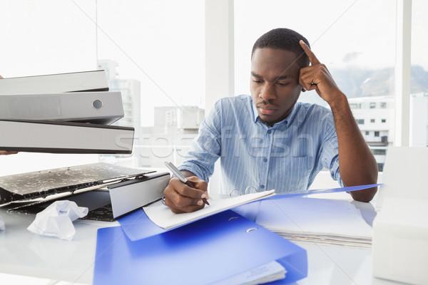 Tired businessman writing notes at desk Stock photo © wavebreak_media