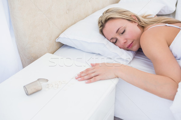 Blonde woman lying motionless in bed after overdose Stock photo © wavebreak_media