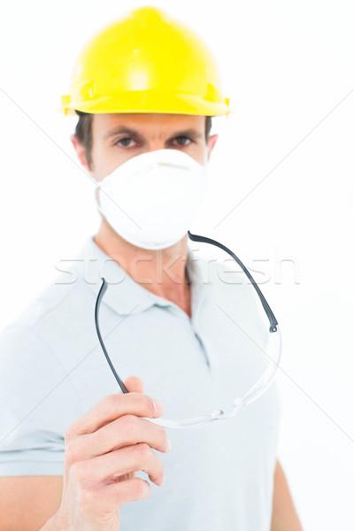 Worker wearing mask and hardhat while holding protective glasses Stock photo © wavebreak_media