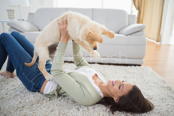 Woman lifting puppy while lying on rug Stock photo © wavebreak_media
