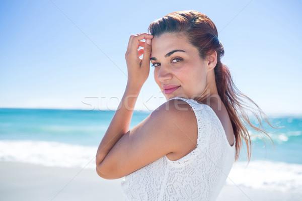 Mooie brunette ontspannen naast water strand Stockfoto © wavebreak_media