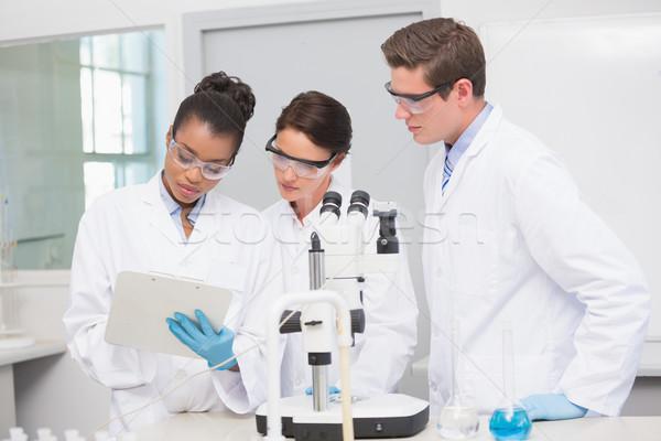 Scienziati lavoro microscopio prendere appunti laboratorio medici Foto d'archivio © wavebreak_media