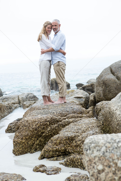 Happy couple standing on the rock and looking at camera Stock photo © wavebreak_media