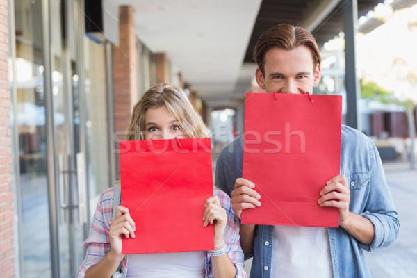 Heureux couple cacher derrière rouge sacs Photo stock © wavebreak_media