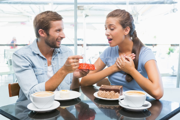 Young happy couple eating cake and man giving her a ring Stock photo © wavebreak_media