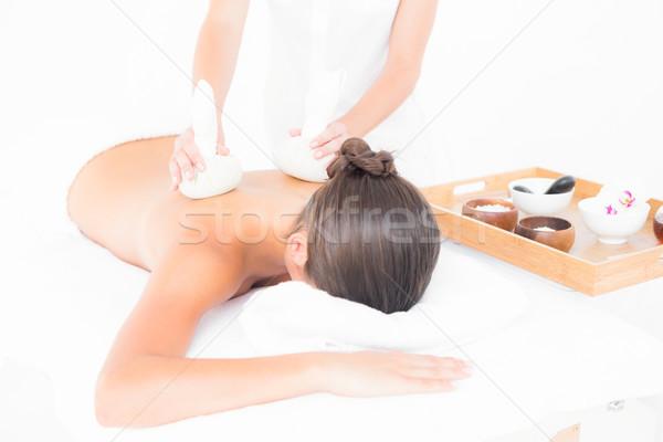 Beautiful brunette enjoying a herbal compress massage Stock photo © wavebreak_media