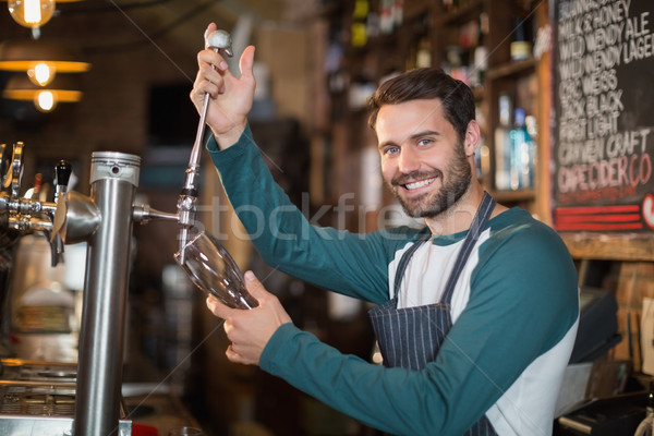 Portrait of bartender pouring beer from tap Stock photo © wavebreak_media