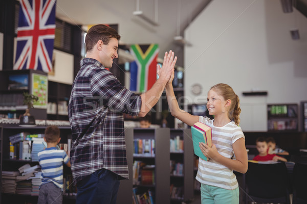 Happy teacher and schoolgirl giving high five in library Stock photo © wavebreak_media