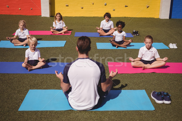Coach and schoolkids practicing yoga Stock photo © wavebreak_media